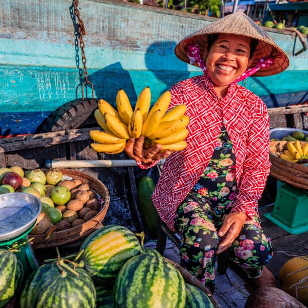 Vietnamese woman selling bananas on floating market, Mekong River Delta, Vietnam Vietnamese woman selling bananas on floating market, Mekong River Delta, Vietnam vietnamese culture stock pictures, royalty-free photos & images