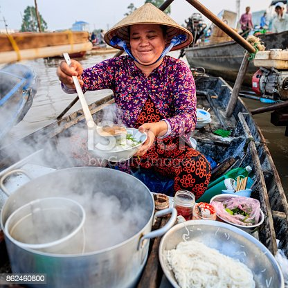 Vietnamese woman selling famous pho bo -noodle soup, floating market on Mekong River Delta, South Vietnam. Pho bo is a extremely popular Vietnamese noodle soup consisting of broth, rice noodles, herbs and beef meat.