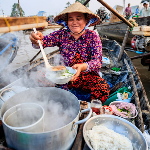vietnamese woman selling famous noodle soup, floating market, mekong river delta, vietnam - pho soup stock photos and pictures