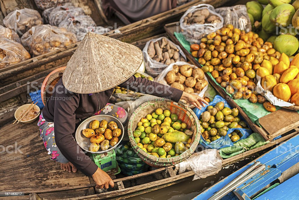 Vietnamese woman selling fruit on floating market, Mekong River Delta, stock photo