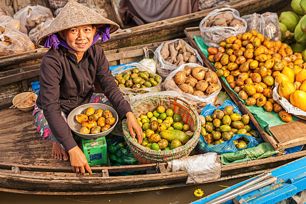 vietnamese woman selling fruit on floating market, mekong river delta, - mekong river stock pictures, royalty-free photos & images