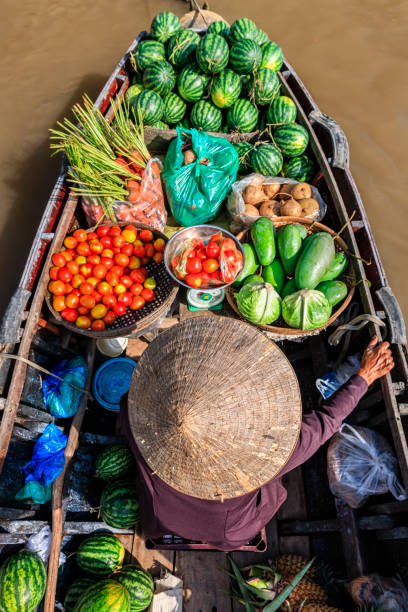 Vietnamese woman selling fruits on floating market, Mekong River Delta, Vietnam stock photo