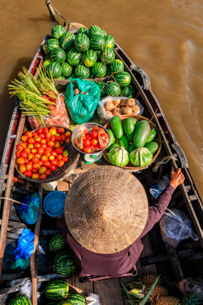 Vietnamese woman selling fruits on floating market, Mekong River Delta, Vietnam Vietnamese woman selling fruits on floating market, Mekong River Delta, Vietnam vietnamese culture stock pictures, royalty-free photos & images