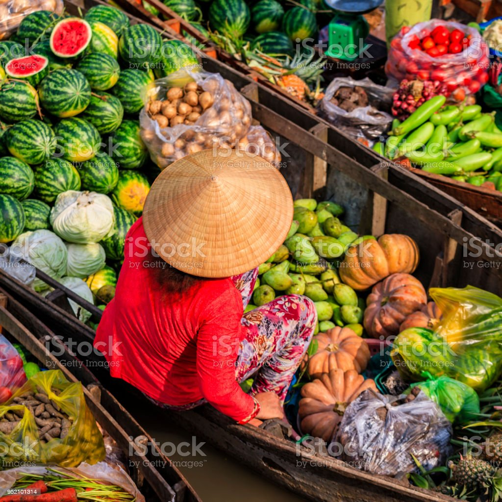 Vietnamese woman selling fruits on floating market, Mekong River...