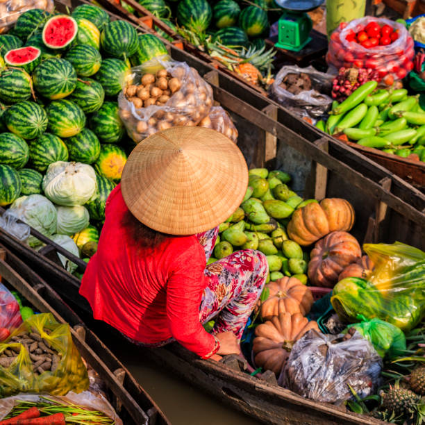 vietnamese woman selling fruits on floating market, mekong river delta, vietnam - mekong river stock pictures, royalty-free photos & images