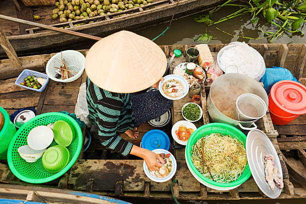 Vietnamese woman selling  Pho - noodle soup on floating market Vietnamese Pho seller on floating market - woman selling noodle soup from her boat in the Mekong river delta, Vietnam. vietnamese culture stock pictures, royalty-free photos & images