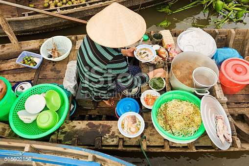 Vietnamese Pho seller on floating market - woman selling noodle soup from her boat in the Mekong river delta, Vietnam.