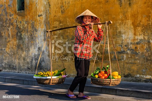 istock Vietnamese woman selling tropical fruits, old town in Hoi An city, Vietnam 864307598
