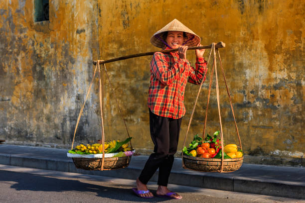 Vietnamese woman selling tropical fruits, old town in Hoi An city, Vietnam Vietnamese woman selling tropical fruits, old town in Hoi An city, Vietnam. Hoi An is situated on the east coast of Vietnam. Its old town is a UNESCO World Heritage Site because of its historical buildings. market vendor stock pictures, royalty-free photos & images