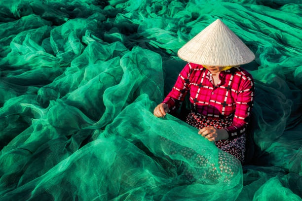 vietnamese woman sitting repair the fish net. - aquaculture stock pictures, royalty-free photos & images