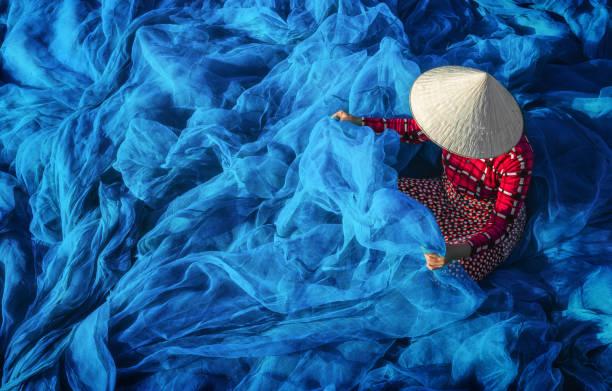 Vietnamese woman sitting repair the fish net. stock photo