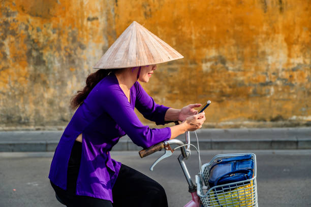 vietnamese woman using mobile phone on a bicycle, old town in hoi an city, vietnam - ao dai stock photos and pictures