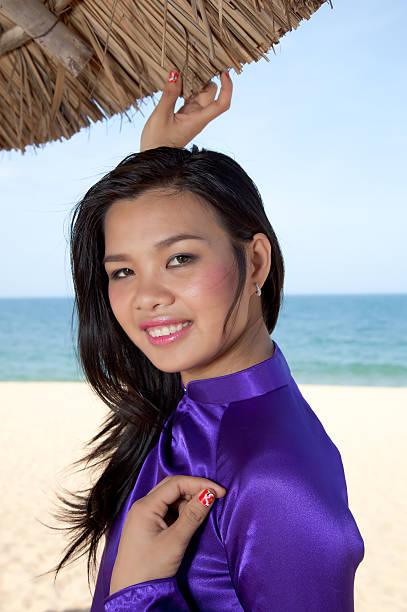 vietnamese woman wearing tradititional aodai dress on nha trang beach - ao dai stock photos and pictures