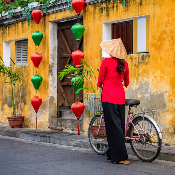 vietnamese woman with a bicycle, old town in hoi an city, vietnam - ao dai stock photos and pictures