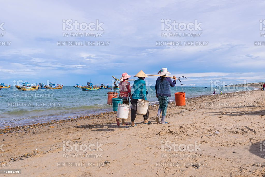 Vietnamese women carry shoulder pole balanced with two plastic pail stock photo