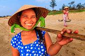 Vietnamese women carrying fruits on the beach, Vietnam