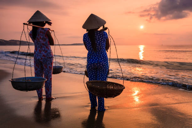 vietnamese women carrying fruits on the beach, vietnam - ao dai stock photos and pictures