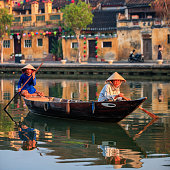 Vietnamese women paddling in old town in Hoi An city, Vietnam