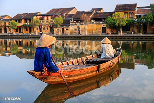 Vietnamese women paddling in old town in Hoi An city, Vietnam. Hoi An is situated on the east coast of Vietnam. Its old town is a UNESCO World Heritage Site because of its historical buildings.