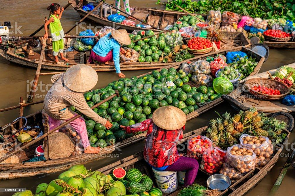 Vietnamese women selling fruits on floating market, Mekong River Delta, Vietnam Vietnamese women selling and buying fruits on floating market, Mekong River Delta, Vietnam Adult Stock Photo
