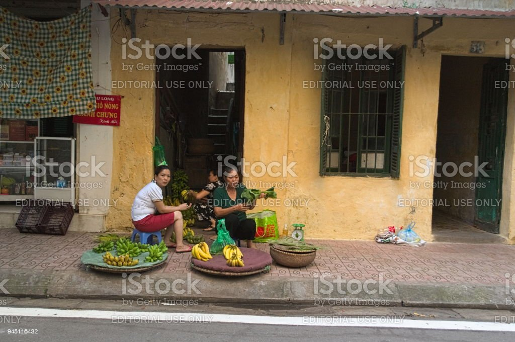 Vietnamese women sells local fruits and vegetables stock photo