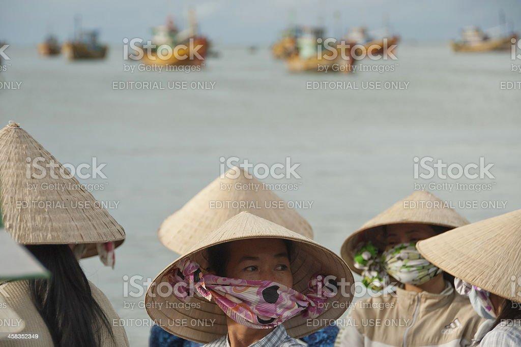 Vietnamese women wait fishing boats in Mui Ne, Vietnam. royalty-free stock photo