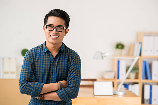 Vietnamese young man Smiling Vietnamese young man in glasses looking at camera vietnamese ethnicity stock pictures, royalty-free photos & images