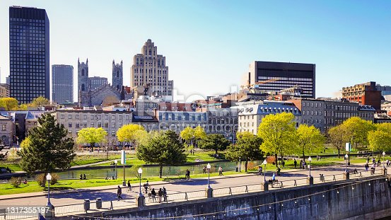 Vieux port de Montreal and downtown skyline with promenade pier on a clear May Springtime day with people walking in the distance