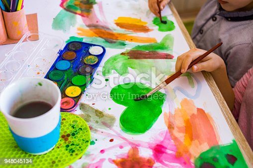 123500924 istock photo View above on the table where children drawing with watercolors 948045134