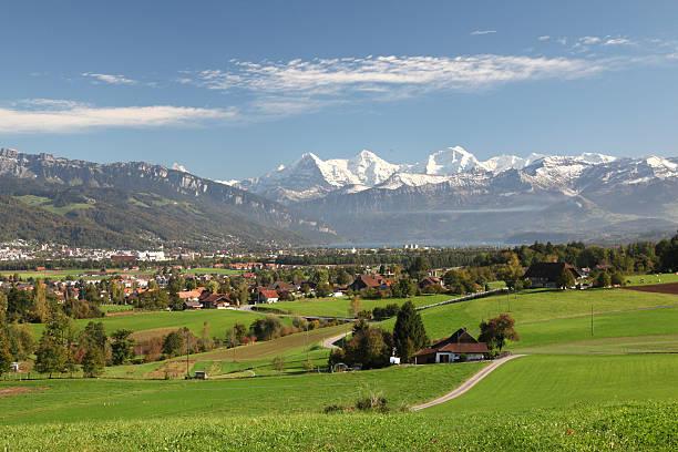 blick über felder in schweizer alpen und interlaken - thun switzerland stock-fotos und bilder
