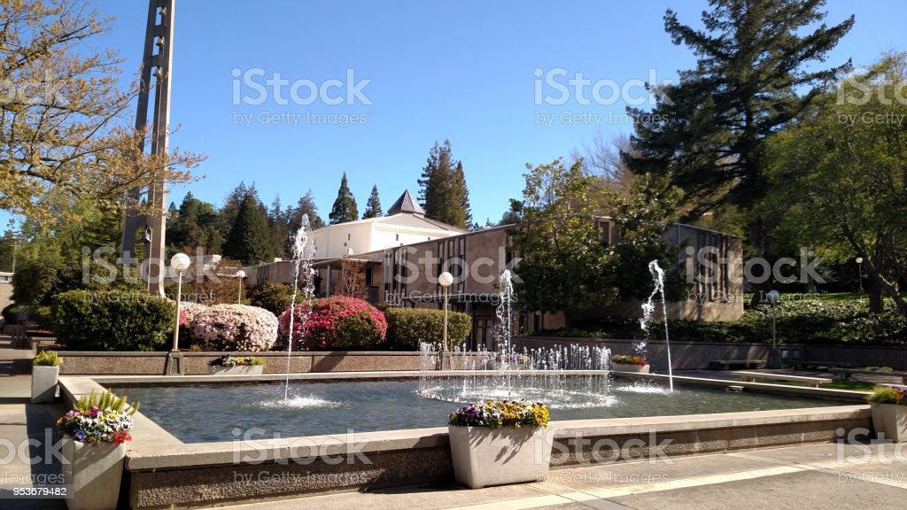 View across fountain toward church and bell tower on central plaza on campus of Pacific Union College Angwin California stock photo