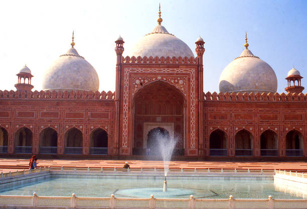 View across fountains in courtyard toward domes of Badshahi Mosque in Lahore Pakistan View across fountains in courtyard toward domes of Badshahi Mosque in Lahore Pakistan lahore pakistan stock pictures, royalty-free photos & images