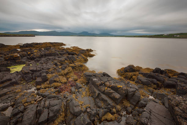 View across rocks and lake to hills stock photo