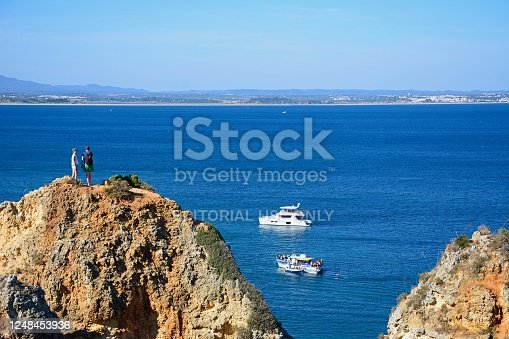 Elevated view of tourists standing on the cliffs with boats in the bay, Ponta da Piedade, Lagos, Algarve, Portugal, Europe.