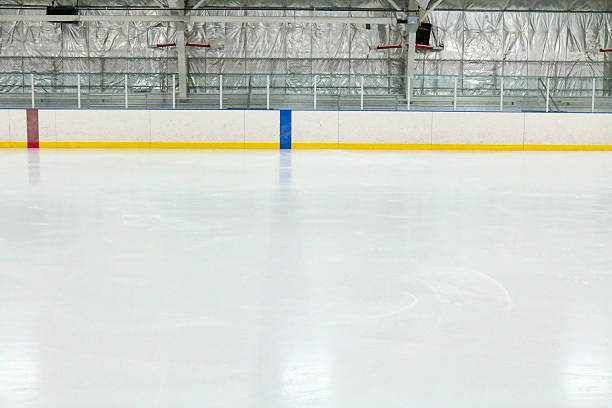 View across the empty ice at an indoor hockey rink Photograph across the empty ice at an indoor hockey rink.  Through the glass, metal bleachers can be seen in this small town hockey arena.  The camera is lined up with the blue line, which is through the ice and on the boards.  The red center line can also be seen.  The ice reflects the lights. ice rink stock pictures, royalty-free photos & images