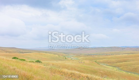 Billings, Montana, USA. View across the rolling landscape of the prairie and a dry riverbed on an overcast day near Billings, Montana, USA.