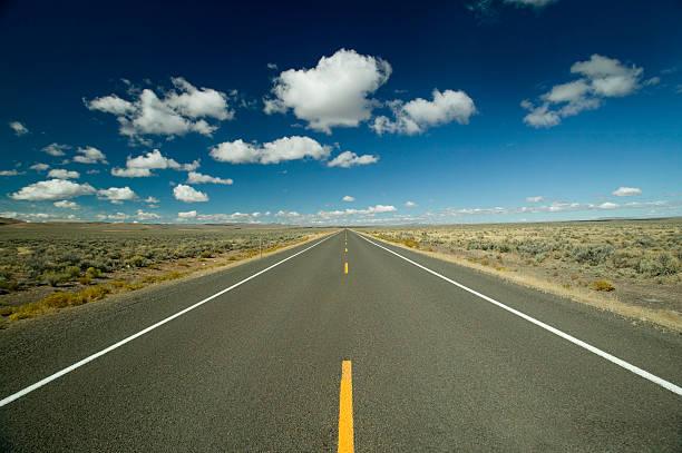 lange, gerade straße mit horizont blauen himmel und weiße wolken - zweispurige strecke stock-fotos und bilder