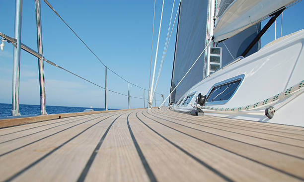 View along teak deck on a sailboat View along teak deck on a sailboat rigging stock pictures, royalty-free photos & images