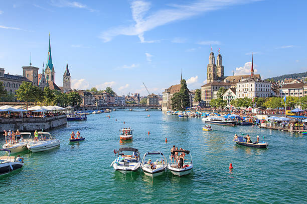 View along the Limmat river during the Street Parade in Zurich Zurich, Switzerland - 2 August, 2014: people in boats on the Limmat river during the Street Parade. The Street Parade is the most attended technoparade in Europe, it takes place in Zurich, Switzerland.  limmat river stock pictures, royalty-free photos & images