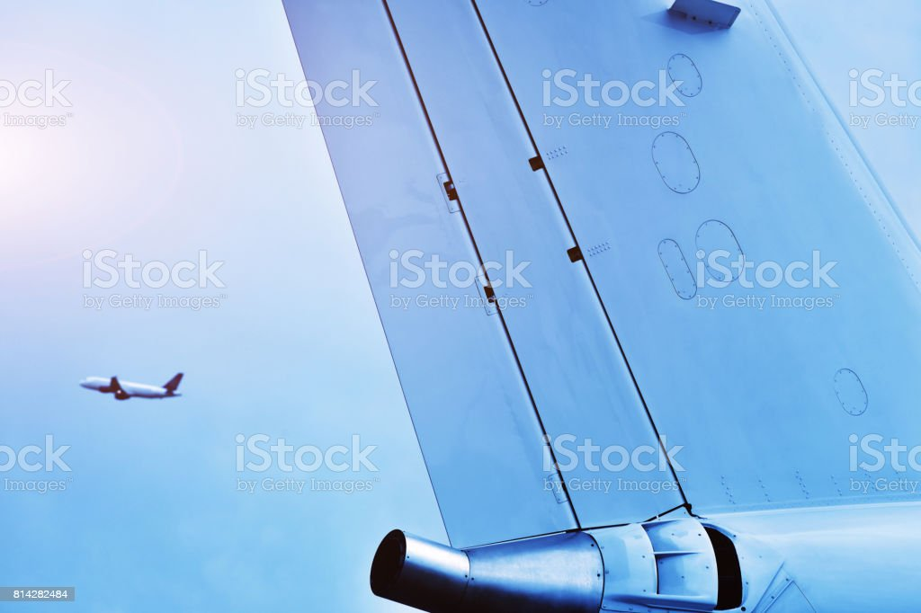 View Another Aircraft Flying Directly Above the Aircraft Empennage stock photo