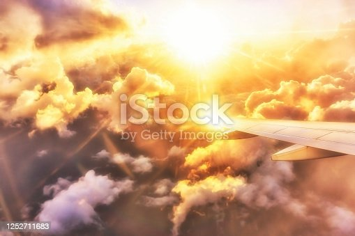 1045890176 istock photo View at a shining airplane wing at sunset over the clouds 1252711683