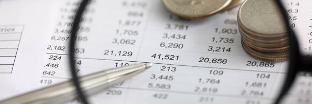 View at financial details in table thru magnifying glass stock photo