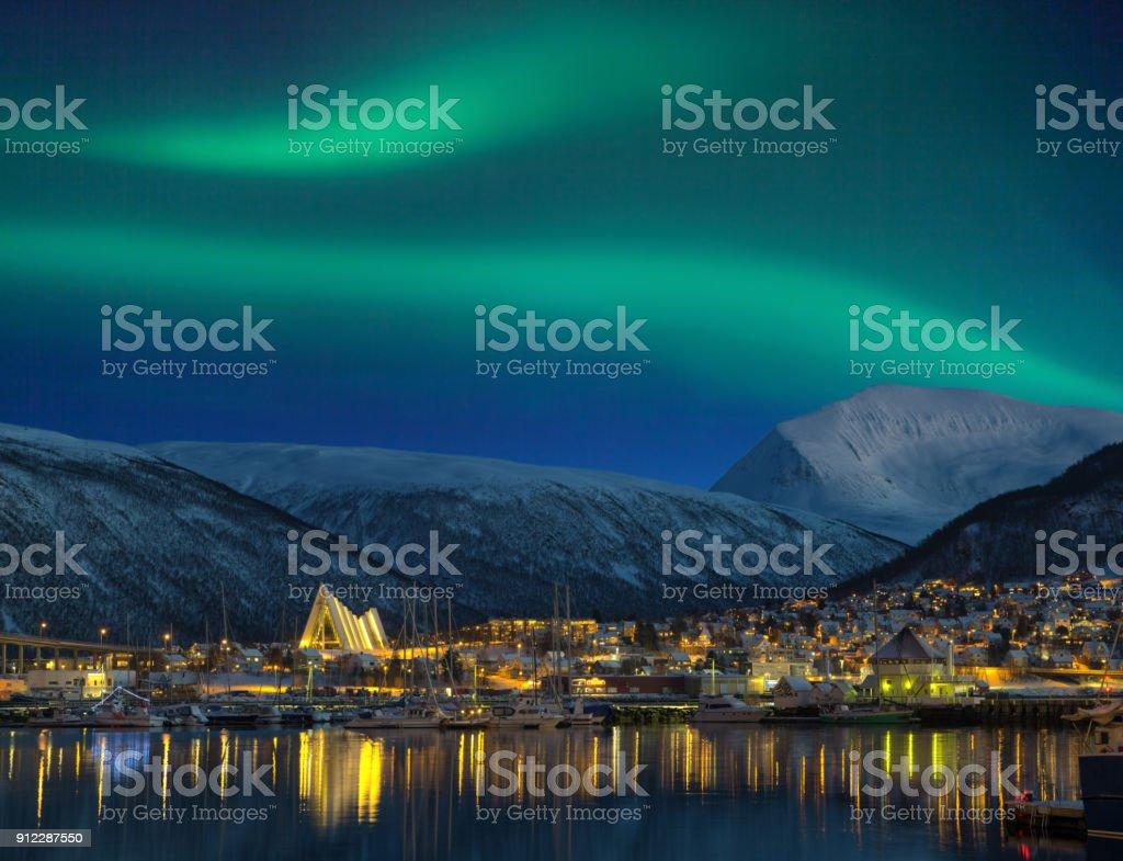 Blick bei Nacht auf beleuchteten Tromso Stadt mit Kathedrale und majestätischen Aurora borealis – Foto