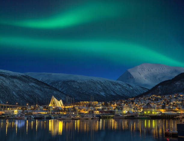 View at night on illuminated Tromso city with cathedral and majestic aurora borealis stock photo