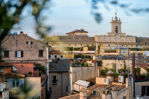A suggestive view at sunset over the rooftops of Rome with the bell and clock tower of the Montecitorio Palace, in the ancient Rione Pigna (Pigna District), in the historic heart of the Eternal City. Originally built in 1653 on a project by Gian Lorenzo Bernini for the Ludovisi family, in 1918 the Palazzo Montecitotio was inaugurated as the seat of the Italian Chamber of Deputies  (Camera Dei Deputati) with the construction of the legislative hemicycle in Art Nouveau style by the architect Ernesto Basile. In 1980 the historic center of Rome was declared a World Heritage Site by Unesco. Image in high definition format.