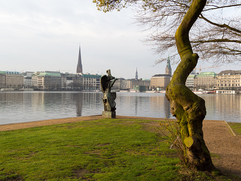 View at tree and sculpture named Windsbraut, whirlwind and Binnenalster and Jungfernstieg in Hamburg, Germany.