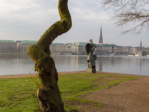 View at tree and sculpture named Windsbraut, whirlwind and Binnenalster in Hamburg, Germany.