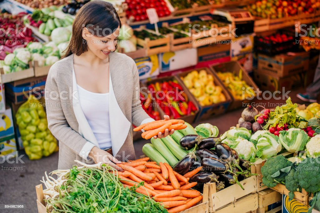 View at young woman buying vegetables at the market. stock photo