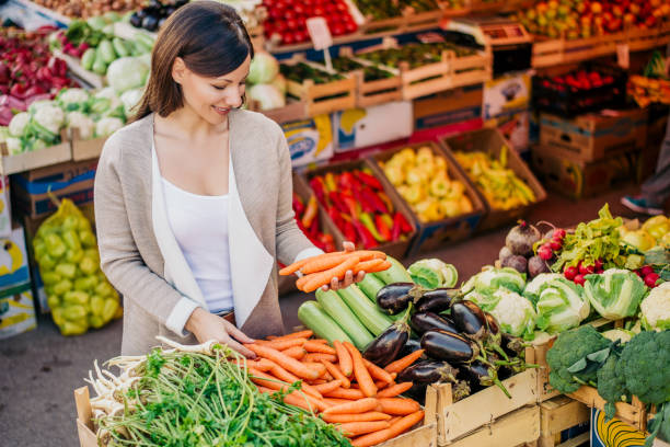 view at young woman buying vegetables at the market. - farmers market stock pictures, royalty-free photos & images