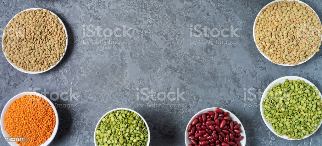 Top view of assortment of peas, lentils, beans and legumes over gray...